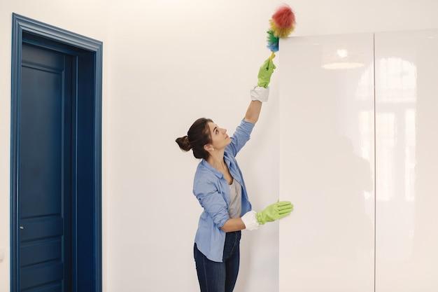 Mulher com esponja e luvas de borracha limpando a casa Foto gratuita