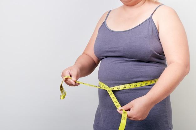 Mulher com excesso de peso, medindo sua barriga gorda Foto Premium