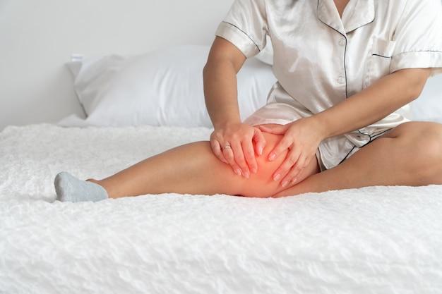 Mulher com excesso de peso, sentada na cama e pegando os joelhos Foto Premium