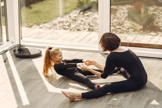 Mulher com filha está envolvida em ginástica Foto gratuita