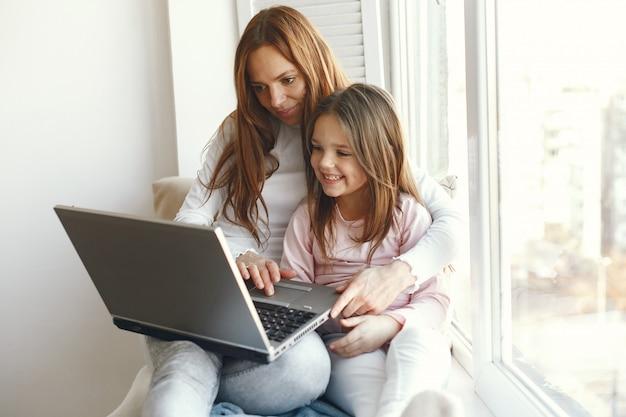 Mulher com filha usando laptop Foto gratuita