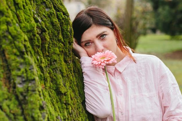 Mulher, com, flor, perto, rosto, apoiando árvore, parque Foto gratuita