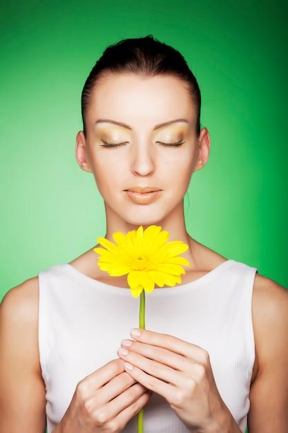 Mulher com flores amarelas em verde Foto Premium