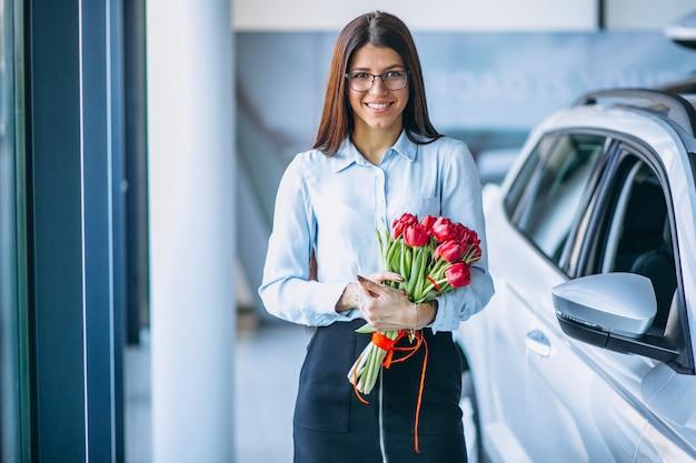 Mulher, com, flores, em, um, showroom carro Foto gratuita