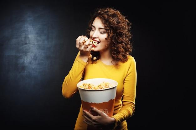 Mulher com fome come um punhado de pipoca enquanto aguarda o filme Foto gratuita