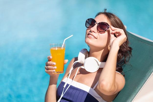Mulher com fones de ouvido e bebida deitado no salão Foto gratuita