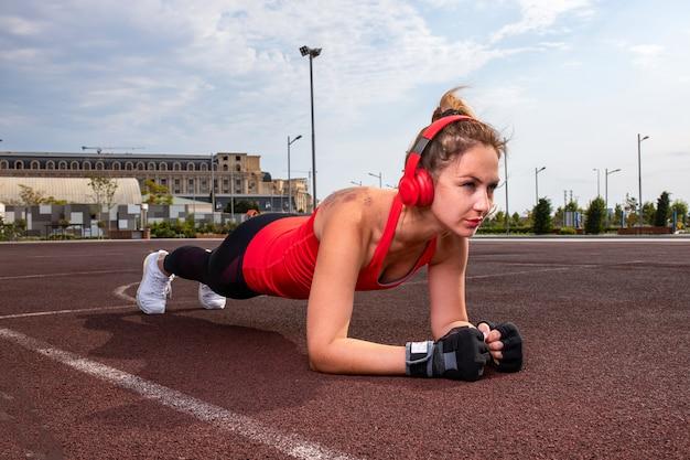 Mulher com fones de ouvido vermelhos e roupas de esporte, fazendo exercícios de ginástica. Foto gratuita