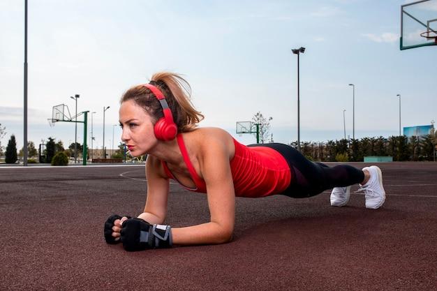 Mulher com fones de ouvido vermelhos fazendo exercícios abdominais na terra no parque. Foto gratuita