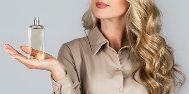 Mulher com frasco de perfume. mulher apresenta fragrância de perfumes. Foto Premium