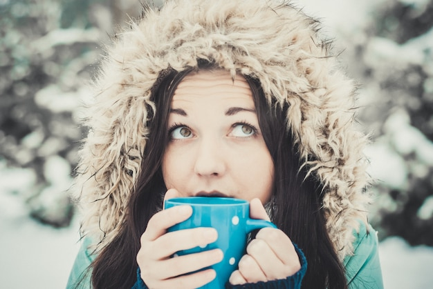 Mulher com grande caneca azul de bebida quente durante o dia frio. Foto Premium