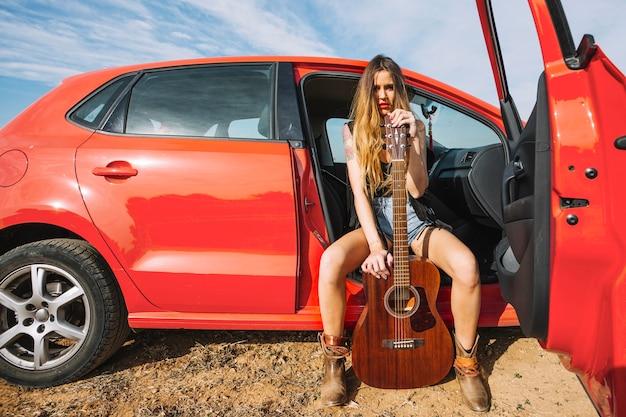 Mulher com guitarra no carro Foto gratuita