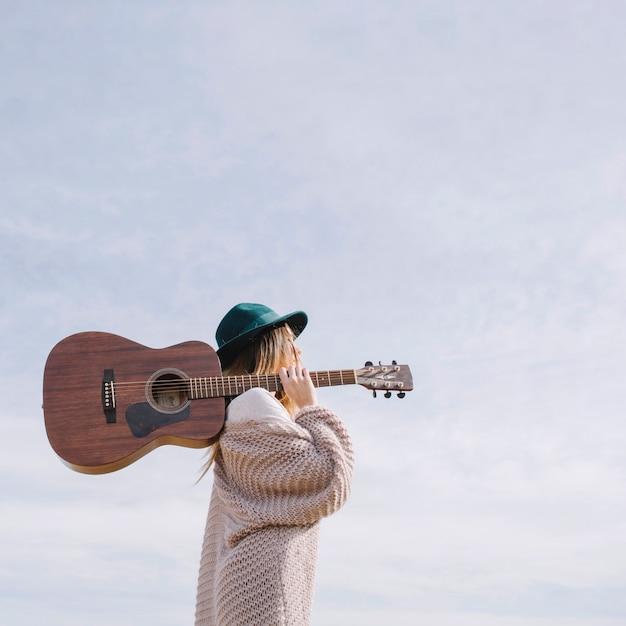 Mulher com guitarra no fundo do céu Foto gratuita