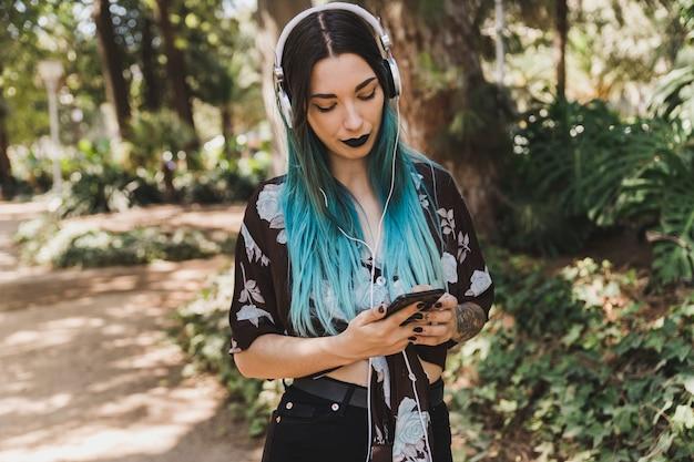 Mulher, com, headphone, ligado, dela, cabeça, usando, telefone móvel Foto gratuita