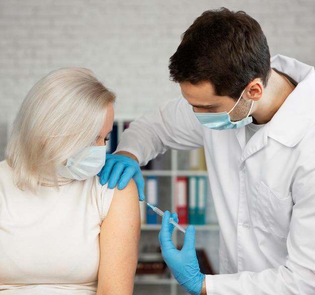 Mulher com injeção média recebendo vacina Foto gratuita