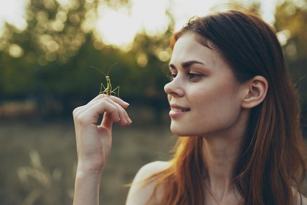 Mulher com inseto na mão rezando árvores natureza louva-a-deus verão Foto Premium