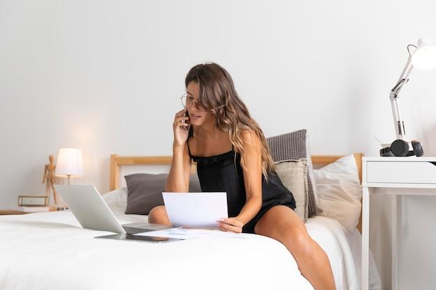 Mulher com laptop na cama falando ao telefone Foto gratuita