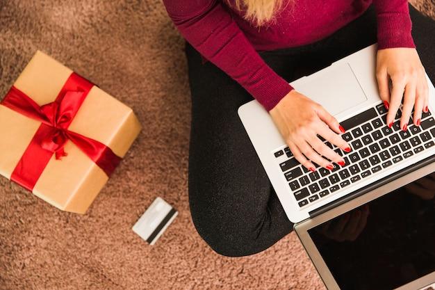 Mulher com laptop perto de cartão de plástico e caixa de presente Foto gratuita