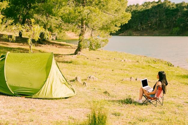 Mulher, com, laptop, sentando, perto, barraca Foto gratuita