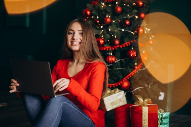 Mulher com laptop sente-se pela árvore de natal Foto gratuita