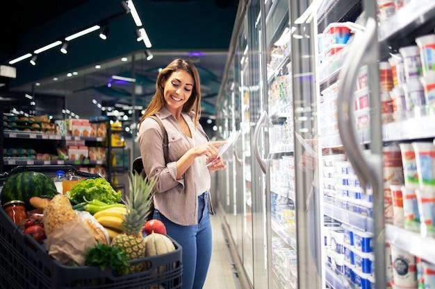 Mulher com lista de compras em pé ao lado da geladeira no supermercado e verificando o carrinho Foto gratuita