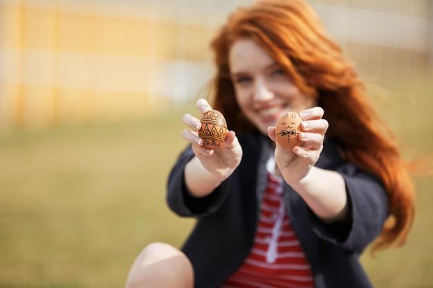 Mulher com longos cabelos ruivos, mostrando dois ovos de páscoa pintados Foto gratuita