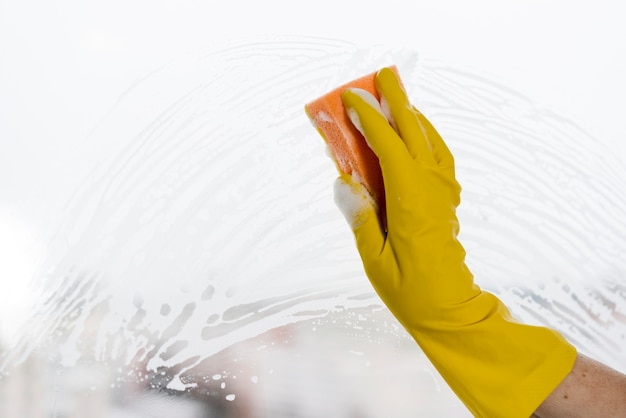 Mulher com luva de borracha, limpeza de janela Foto gratuita