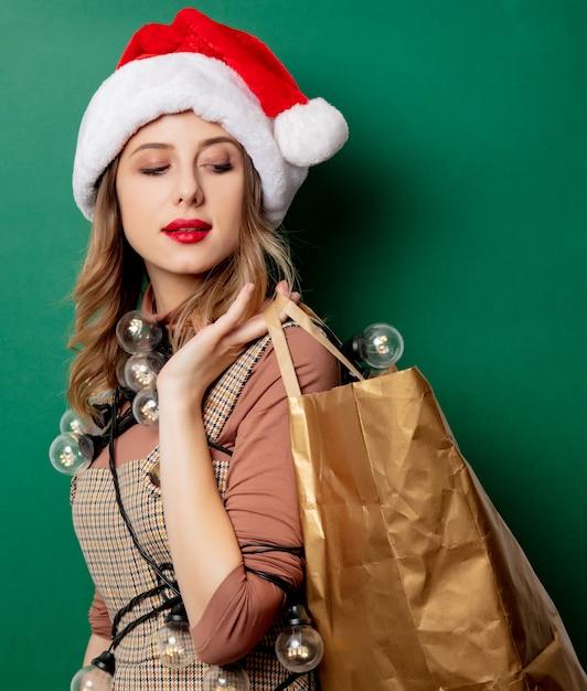 Mulher com luzes de natal e sacola de compras Foto Premium