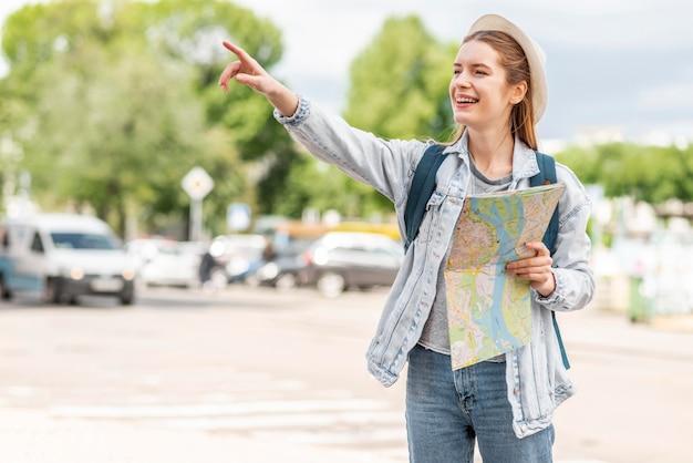Mulher com mapa apontando o dedo no ar Foto gratuita