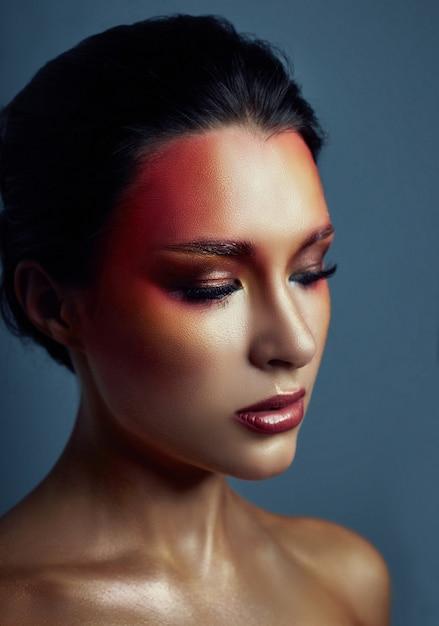 Mulher com maquiagem brilhante vermelha no rosto e olhos Foto Premium
