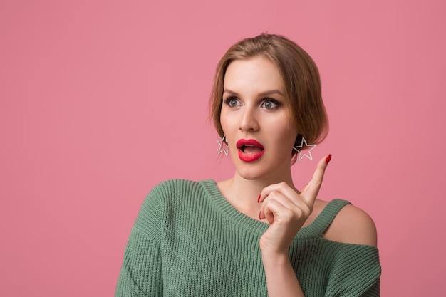 Mulher com maquiagem elegante, lábios vermelhos, suéter verde posando em rosa Foto gratuita