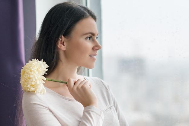 Mulher com maquiagem natural, com grande flor amarela pálida Foto Premium