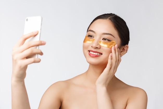 Mulher com máscara de olhos tomando selfie com o telefone móvel em casa, desfrutando de relaxamento e Foto Premium