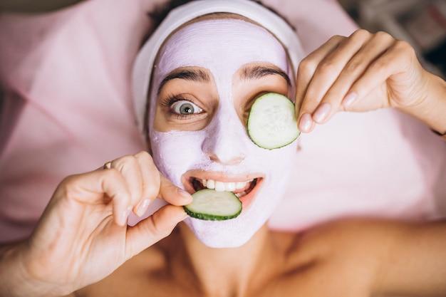 Mulher com máscara e pepino nos olhos Foto gratuita