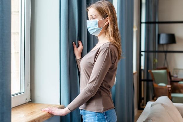 Mulher com máscara em quarentena devido ao coronavírus olhando para as janelas