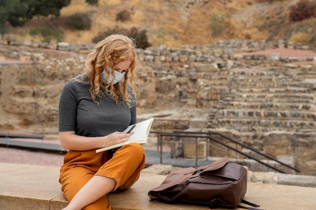 Mulher com máscara escrevendo no diário Foto gratuita