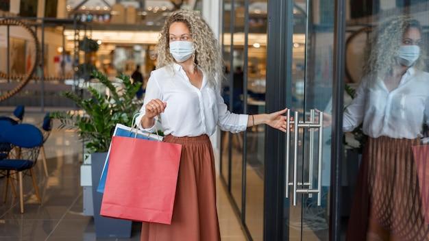 Mulher com máscara facial carregando sacolas de compras Foto gratuita