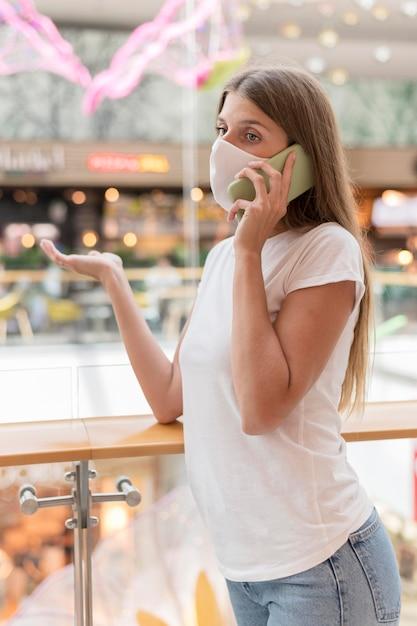 Mulher com máscara facial falando ao telefone no shopping Foto gratuita