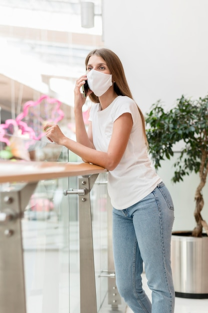 Mulher com máscara facial no shopping falando ao telefone Foto gratuita
