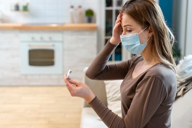 Mulher com máscara, ficar em quarentena, verificando sua temperatura Foto Premium