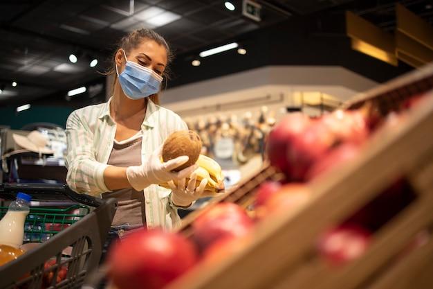 Mulher com máscara higiênica e luvas de borracha e carrinho de compras no supermercado, comprando frutas durante o vírus corona e se preparando para uma quarentena pandêmica Foto gratuita