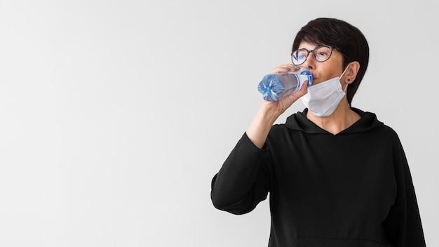 Mulher com máscara médica bebendo água de uma garrafa Foto gratuita
