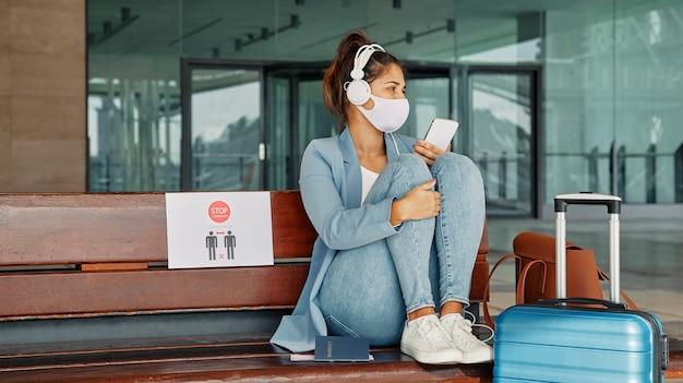 Mulher com máscara médica e fones de ouvido e o aeroporto durante a pandemia Foto Premium