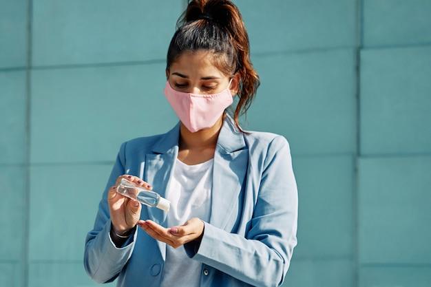 Mulher com máscara médica no aeroporto usando desinfetante para as mãos durante a pandemia Foto gratuita