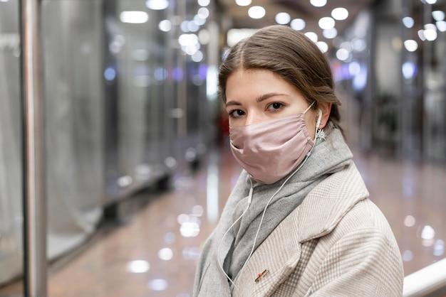 Mulher com máscara médica no shopping da cidade Foto gratuita
