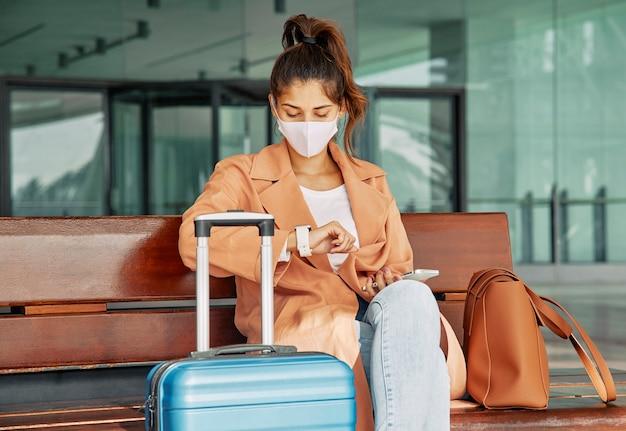 Mulher com máscara médica olhando para o relógio no aeroporto durante a pandemia Foto gratuita