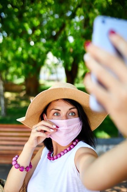 Mulher com máscara médica rosa no parque tira selfie pelo telefone celular Foto Premium