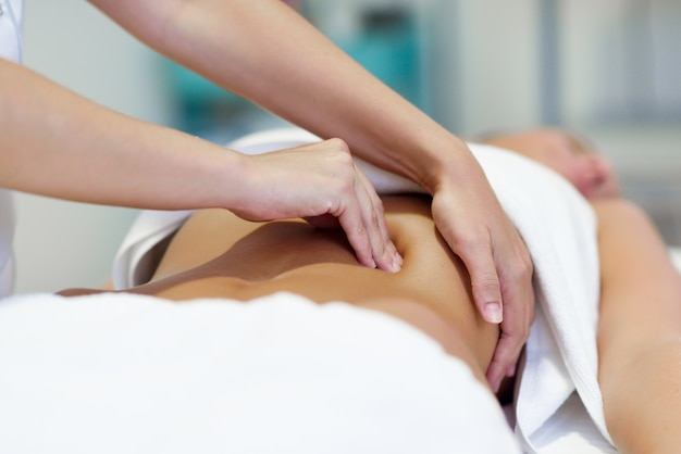 Mulher com massagem no abdômen por terapeuta profissional de osteopatia Foto gratuita