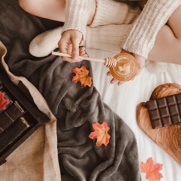Mulher com mel perto de livros e chocolate Foto gratuita