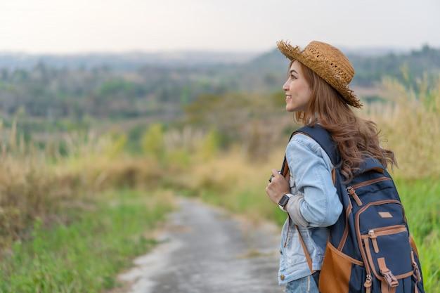 Mulher com mochila caminhando na trilha na natureza Foto Premium