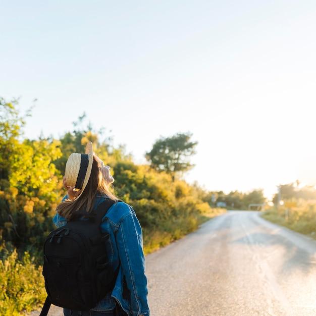 Mulher com mochila e chapéu, admirando a natureza e o sol Foto gratuita